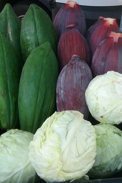 bin of papaya, banana flower, and cabbage at the farmers market