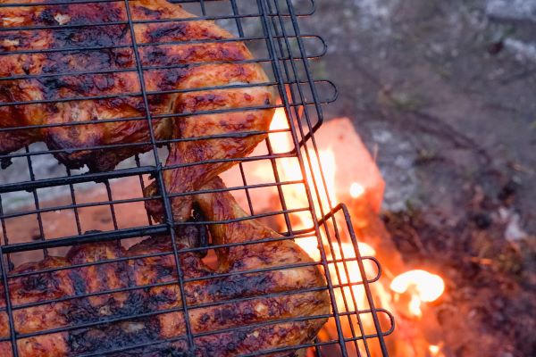 grilling chicken over fire